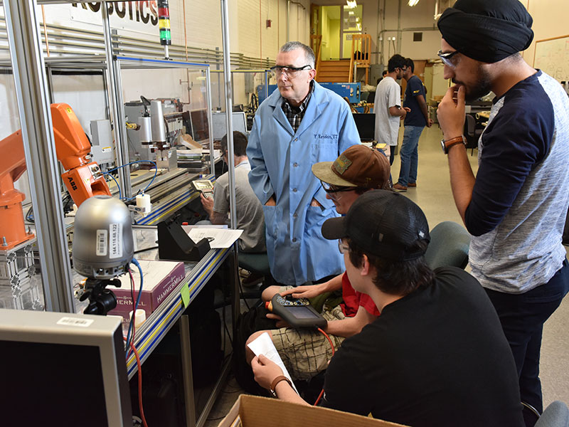 Faculty member working with students in engineering lab