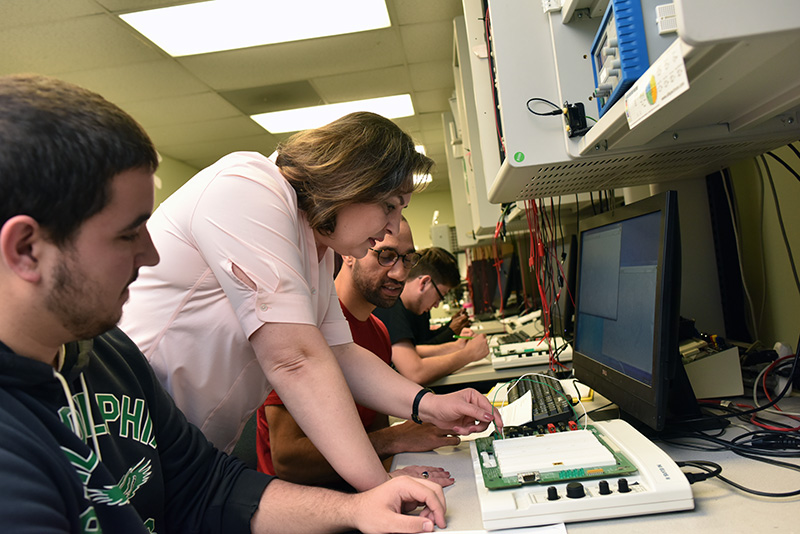 Faculty and students in electronics lab
