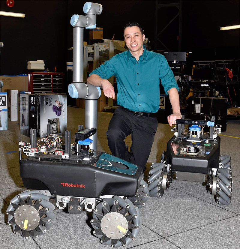 Dr. James Hing working with robots