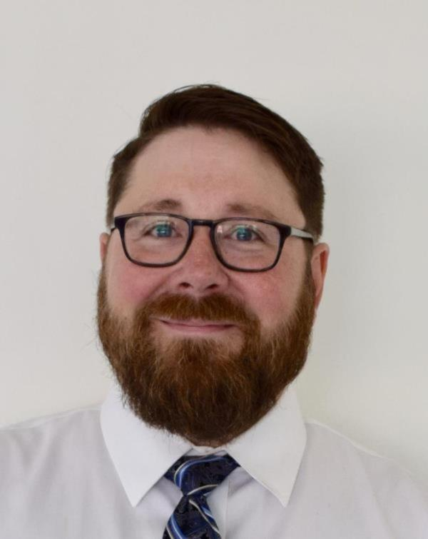 Man in tie with beard and glasses