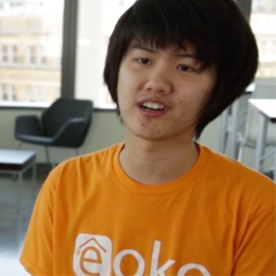 young man with short black hair and orange shirt