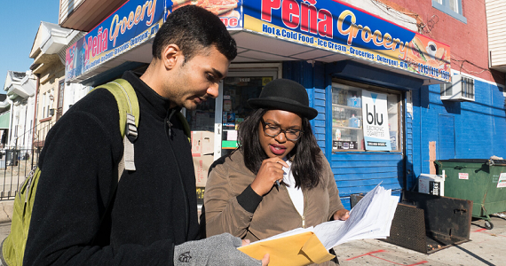 A man and woman reviewing documents on a street corner in Philadelphia