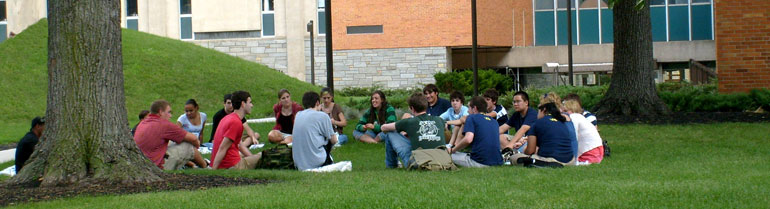 A group discussion with several students sitting on a lawn