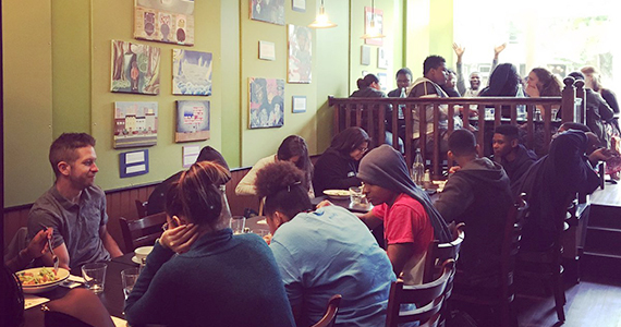 Large group of people sitting at tables at EAT Cafe