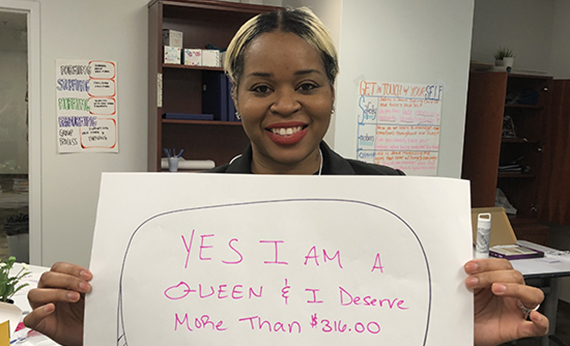 Woman holding sign that says: Yes I am a Queen and I deserve more than $316
