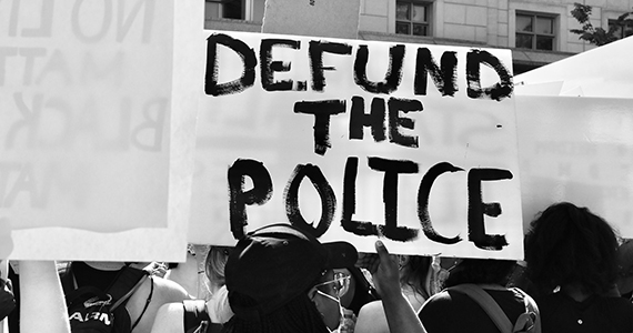 "Protestors Holding Signs that say ""defund the police"""