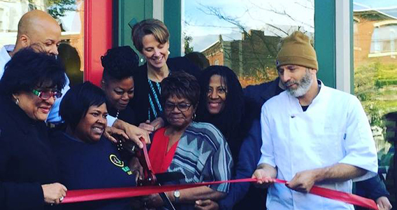 Group of people cutting a ribbon in front of the EAT Cafe