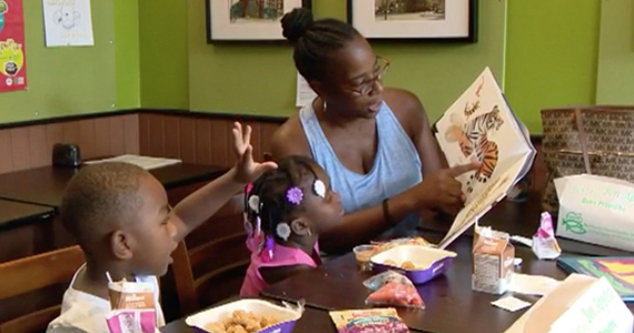 Woman reading a book to two children who are eating