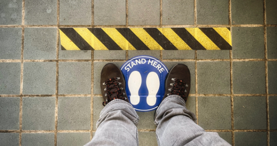 person standing in a social distance floor sticker