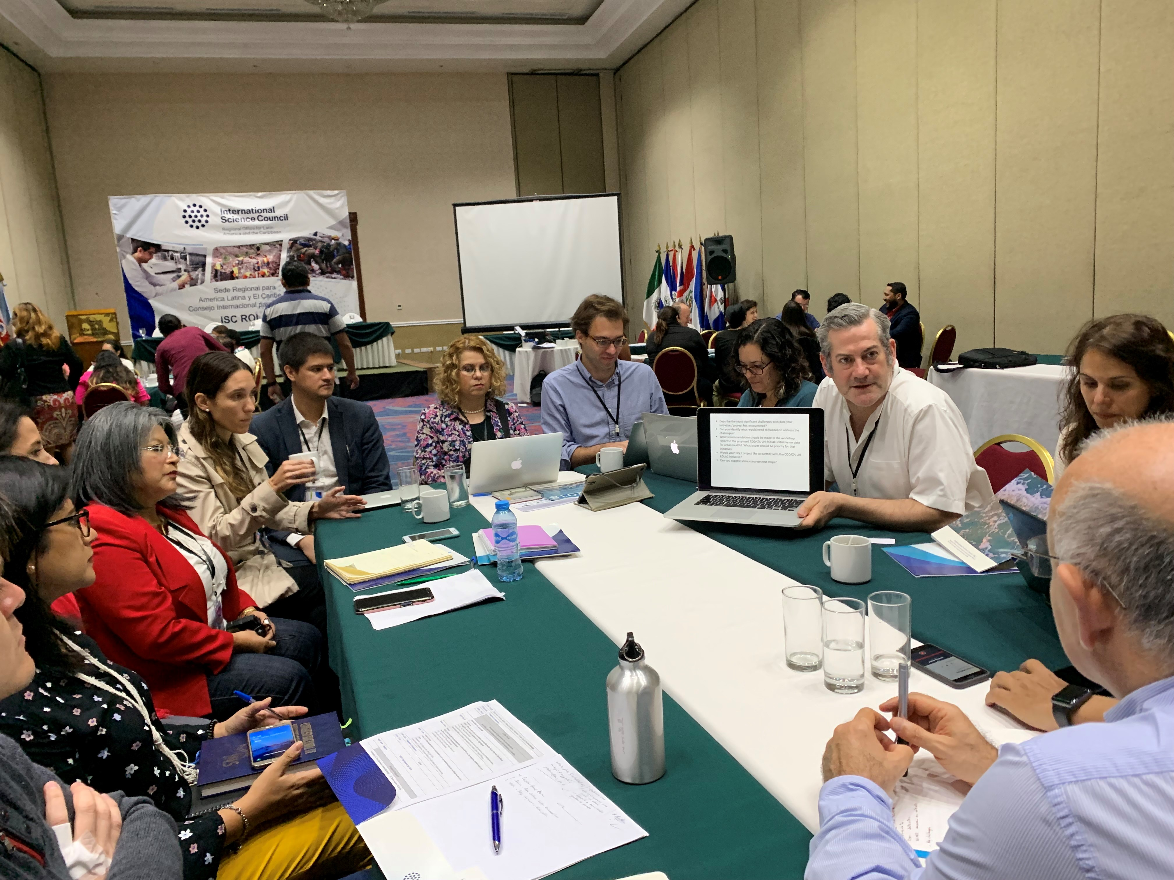 researchers at table discussing health data in latin america