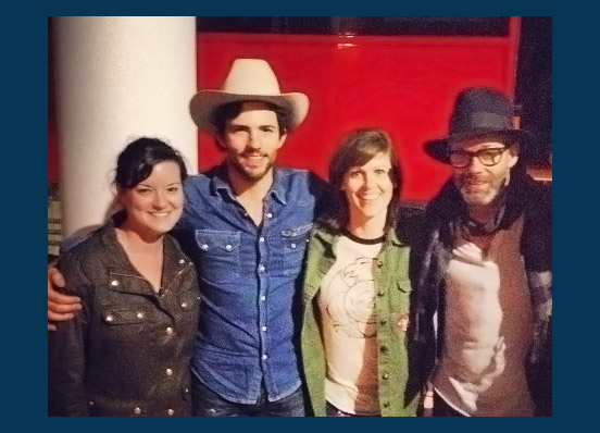 Adria, left, poses with her business partner, Sari Casper, and members of the Avett Brothers band