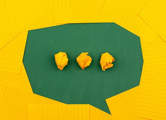 A flat lay of yellow papers forming a dialogue box with crumbled yellow papers in the box in the shape of an ellipsis.