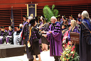 Dean Roger Dennis congratulates new grad at commencement 2016
