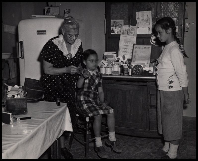 Dr. Lillie Rosa Minoka Hill applying first aid for Carol Hause, while her sister Loretta watches intently.
