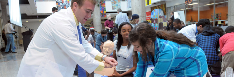 A Drexel medical student/resident at an AHA CPR event demonstrating CPR to kids.