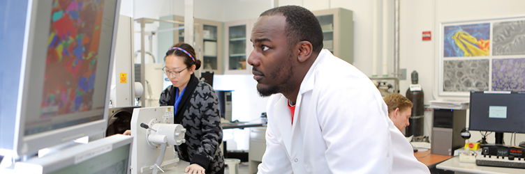 Drexel graduate students working in a biomedical research lab; one student is watching a monitor closely.