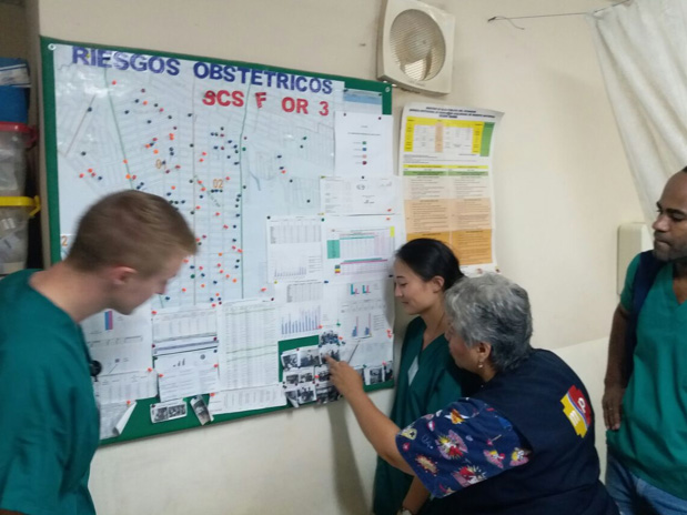 Drexel med student Garrett Mayo in the health clinic of Guayaquil; a board to monitor pregnant patients, including risk level.