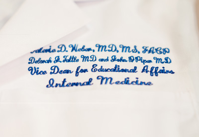 Valerie Weber's white coat embroidered with her new title