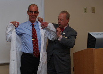 Daniel V. Schidlow, MD, Annenberg Dean of Drexel University College of Medicine, presents a Drexel white coat to Richard Sloan, MD, director of medical education at WellSpan York Hospital
