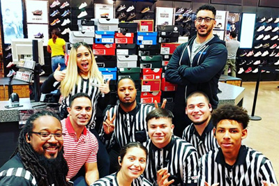 Master of Science in Interdisciplinary Health Sciences (IHS) program graduate student Sam Sayed with staff at Foot Locker in Arlington, Texas.