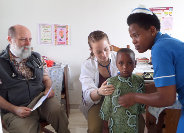 Clare Coda examines a young patient in Uganda as her father looks on.