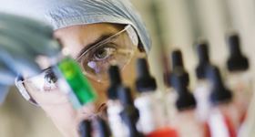 Animal science laboratory technician looking at vials.