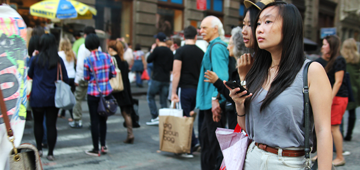 Two young women using mobile phones in a crowded street