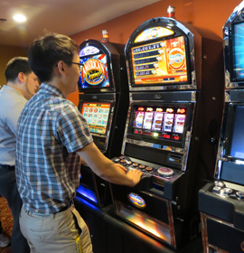Hospitality management majors Vincent Santosusso (L) and Yonghwan Um (R) use the slot machines during a casino management class