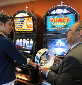 Instructor Bob Ambrose (R) shows hospitality management major Andres Roos a reel strip from one of the machines