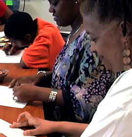 Women and children at the 11th Street Family Health Services draw and write as part of an educational or integrative health program.