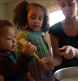 Barbie Izquierdo and her two children cooking at home, as seen in A Place at the Table