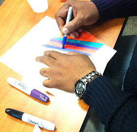 A participant in the Porch Light Initiative draws with colorful markers.