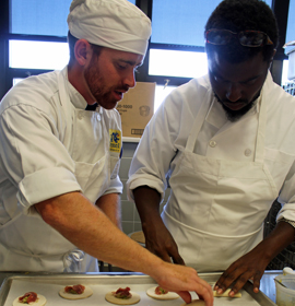 Drexel student Matt Sandrowski and neighborhood resident Tykeem Bond make Chef Feustel's family pierogie recipe