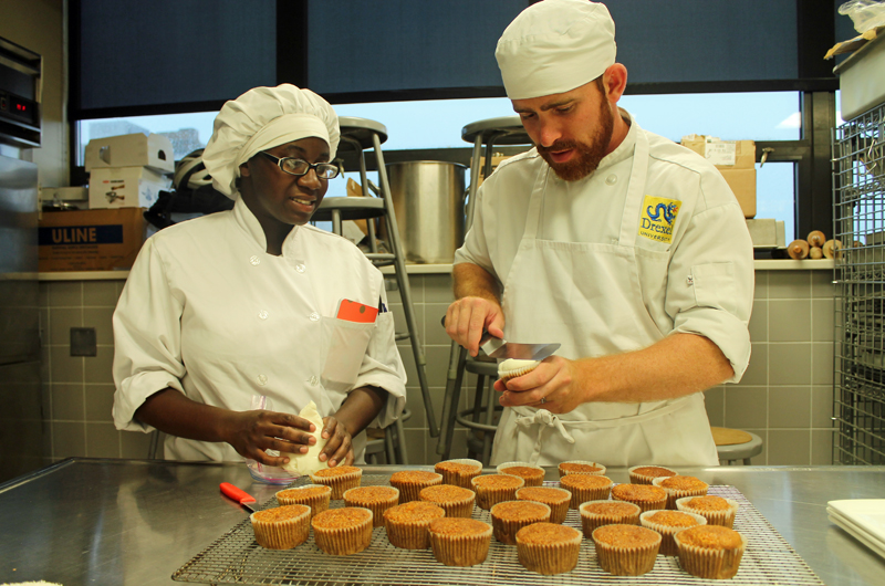 Drexel hospitality management student Matt Sandrowski shows a classmate how to make his mother's carrot cake recipe