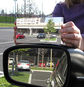 A side-by-side comparison of a standard flat driver's side mirror with the mirror Hicks designed, which has a much wider field of view and minimal image distortion