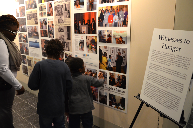 Tianna, a participant in Witnesses to Hunger, reviews some of the program's accomplishments with her children at the program's five-year anniversary exhibit.