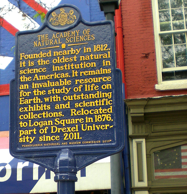 "Historical marker: ""The Academy of Natural Sciences. Founded nearby in 1812, it is the oldest natural science institution in the Americas. It remains an invaluable resource for the study of life on Earth, with outstanding exhibits and scientific collections. Relocated to Logan Square in 1876, part of Drexel University since 2011."""