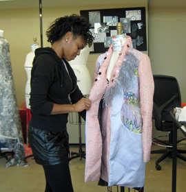 Amber J. Cuff puts the final touches on a jacket from her collection.