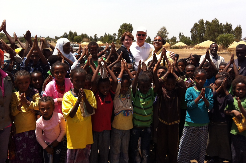 Dana and David Dornsife and Shannon Marquez, PhD, with children and friends at Kechema Water Point in Ethiopia, a World Vision WASH project site.