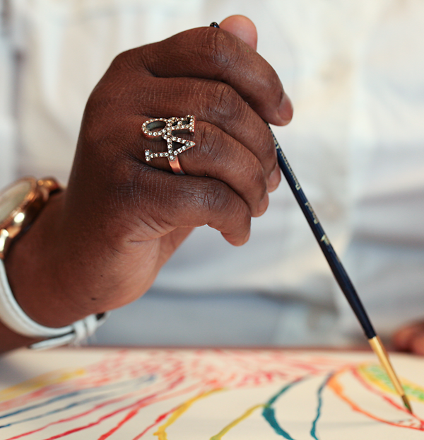 Close-up of a woman's hand, painting as part of a healing-focused effort at Drexel's 11th Street health center. Photo by Lynn Johnson
