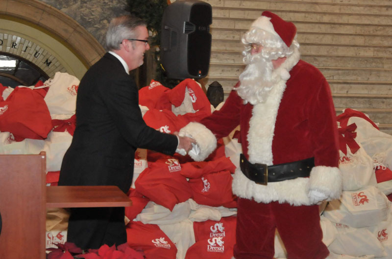 Drexel President John A. Fry shakes hands with Santa Claus at annual toy drive distribution ceremony.