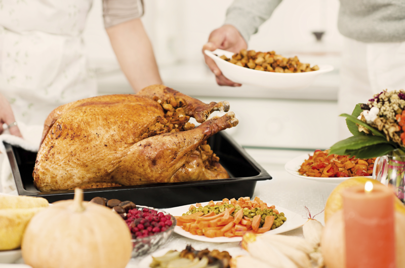 A turkey, carrots, cranberries and other side dishes are placed on a table for a holiday meal.