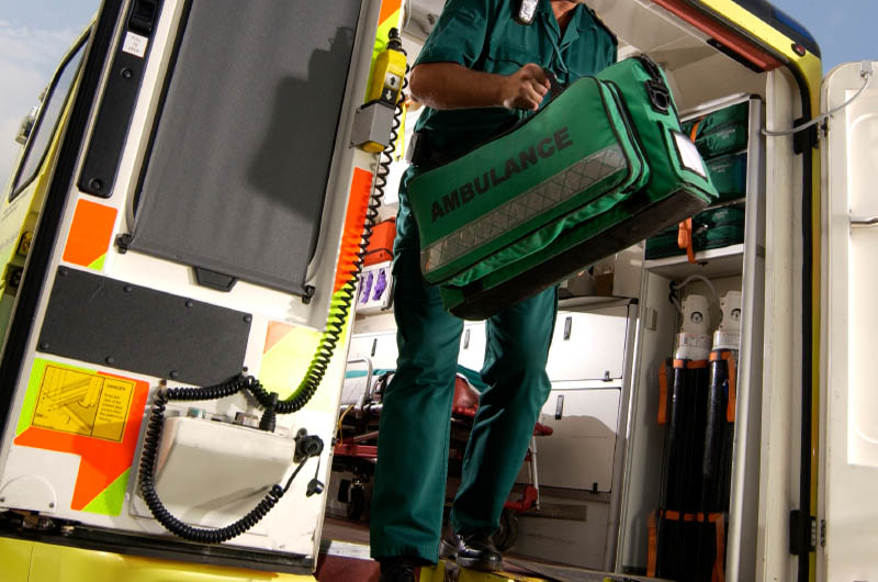 An emergency responder exits an ambulance