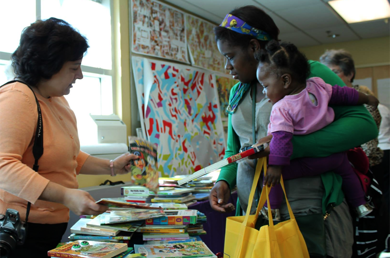 A mother and child receive free children's books at 11th Street Loves to Read Day.