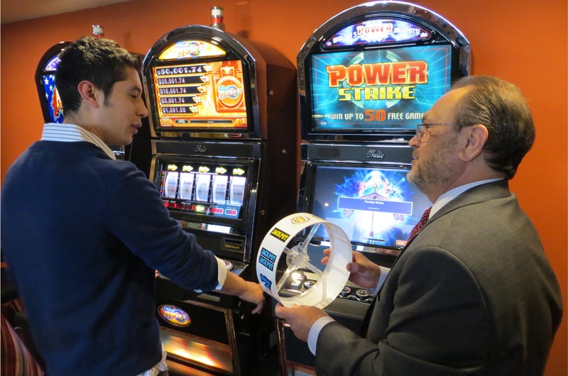 Instructor Bob Ambrose shows hospitality management major Andres Roos a reel strip from one of the slot machines in the Dennis Gomes Memorial Casino Training Lab.