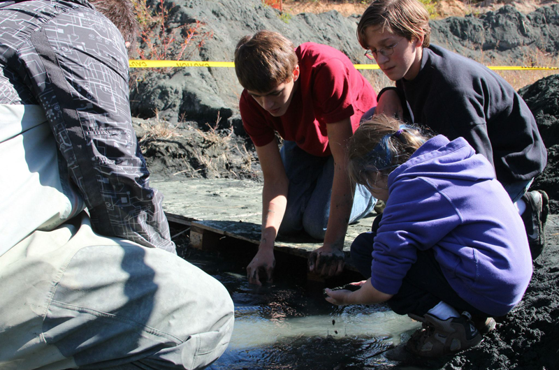 Children and teens dig for fossils.