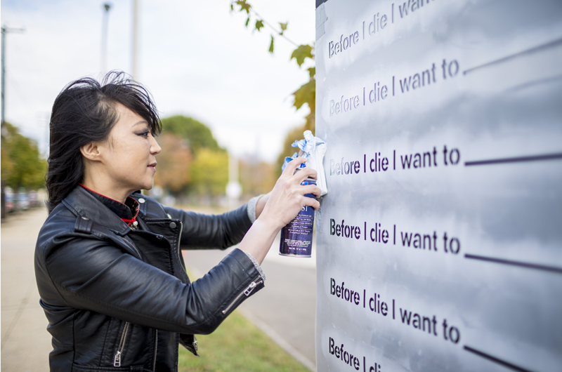 "Chang created a ""Before I die…"" art installation on an 80-foot wall surrounding the construction site of the former University City High School. Photo credit: C. Shan Cerrone."