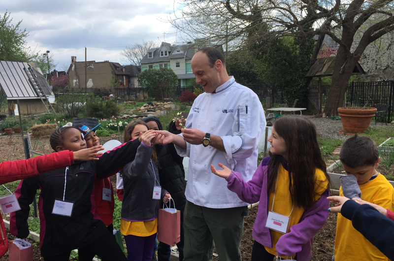 Chef Charles B. Ziccardi, assistant teaching professor of Culinary Arts at Drexel, showing children garden-fresh ingredients during Inspire a Child to Dream Day.