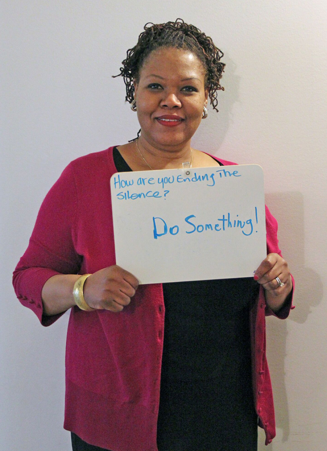 Millie Carvalho-Grevious, PhD, diversity and inclusion coordinator in the Office of Equality and Diversity at Drexel, holding a sign with a message for the National Day of Silence.