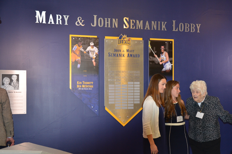 Mary Semanik, far right, in the lobby newly dedicated to her and her husband, John, speaking with former women's lacrosse player Amanda Norcini (center) and the Mary Semanik Head Coach of Women's Lacrosse, Hannah Rudloff (left).